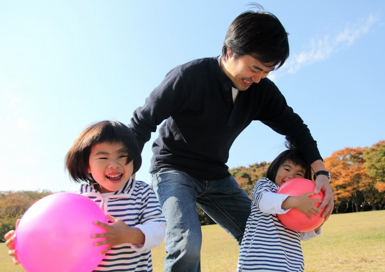 公園で遊ぶ姉妹とお父さん