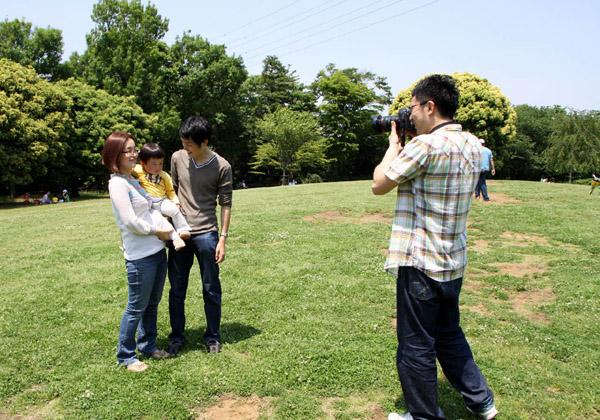 公園で親子を撮影するカメラマン