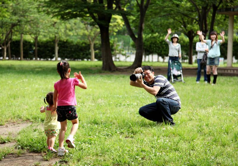 公園で姉妹を撮影するカメラマン